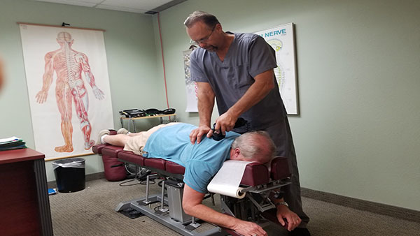 Chiropractor working on patients back at The Get Well Center in Scottsdale AZ